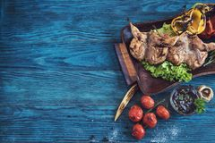 Grilled quail meat. With vegetable on a blue wooden background Stock Image