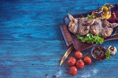 Grilled quail meat. With vegetable on a blue wooden background Stock Photography