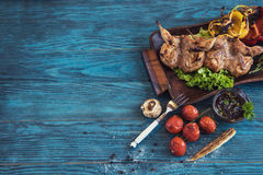 Grilled quail meat. With vegetable on a blue wooden background Royalty Free Stock Photo