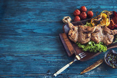 Grilled quail meat. With vegetable on a blue wooden background Stock Images