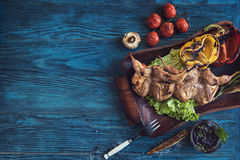 Grilled quail meat. With vegetable on a blue wooden background Royalty Free Stock Photography