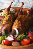 Grilled quail and salad of fresh vegetables close-up. Vertical. Grilled quail and salad of fresh vegetables close-up on a plate. Vertical Royalty Free Stock Photography