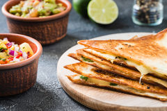 Grilled quesadillas & x28;tortillas& x29; with salsa, guacamole. Dark background Royalty Free Stock Images