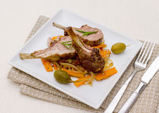 Grilled rack of lamb with olive, capers and carrot Royalty Free Stock Image