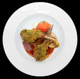 Grilled rack of lamb with pistachio in plate, isolated on black Royalty Free Stock Photo