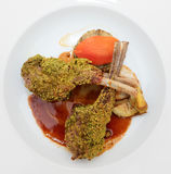 Grilled rack of lamb with pistachio in plate, isolated on black Stock Image