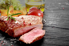 Grilled rare rump steak. Healthy trimmed lean medallion of grilled rare rump steak sliced through to show the texture seasoned with salt and herbs on an old Stock Photography