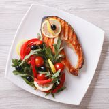 Grilled red fish steak and vegetable salad top view close-up. Grilled red fish steak and vegetable salad on a plate. top view close-up Royalty Free Stock Images