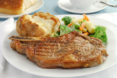 Grilled rib eye steak. A grilled rib eye steak with baked potato and mixed vegetables stock images
