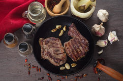 Grilled rib eye steak composition on grill iron pan on wooden background Royalty Free Stock Photos