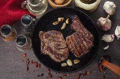 Grilled rib eye steak composition on grill iron pan on wooden background Stock Images