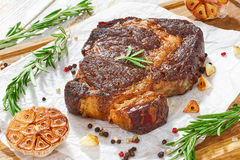 Grilled rib-eye steak with garlic and rosemary on paper. Medium-rare grilled rib-eye steak with garlic and rosemary on paper on wooden background, close-up Royalty Free Stock Photo