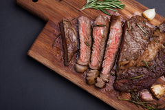 Grilled rib-eye steak of marble beef closeup with spices on a wooden Board. Juicy steak medium sliced and ready to eat. With copy. Grilled ribeye steak of marble Stock Images