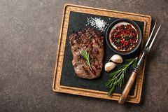 Grilled rib eye steak, spices and vintage meat fork on serving b Royalty Free Stock Photography