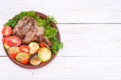 Grilled rib with grilled vegetables. Background. Royalty Free Stock Image