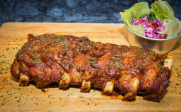 Grilled rib pork with barbecue sauce and vegetable on wooden cutting board. Stock Photos