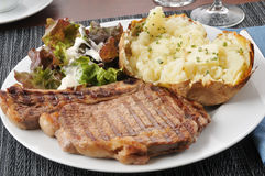 Grilled rib steak with baked potato Royalty Free Stock Images