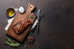 Grilled ribeye beef steak, herbs and spices. Top view with copy space for your text royalty free stock images