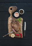Grilled ribeye beef steak with herbs and spices on walnut cutting board over black wooden background Royalty Free Stock Image