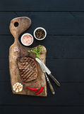 Grilled ribeye beef steak with herbs and spices on walnut cutting board over black wooden background Stock Images
