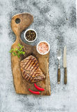 Grilled ribeye beef steak with herbs and spices on walnut cutting board over grunge grey background Stock Image