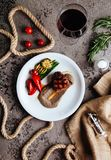 Grilled ribeye beef steak with red wine, herbs and spices on a dark stone background. royalty free stock images
