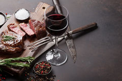 Grilled ribeye beef steak with red wine, herbs and spices. On stone table Stock Photos
