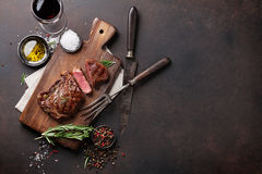 Grilled ribeye beef steak with red wine, herbs and spices. Top view with copy space for your text Royalty Free Stock Photos