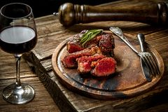 Grilled ribeye beef steak with red wine, herbs and spices on wooden table. Still life Royalty Free Stock Image