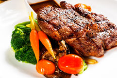 Grilled ribeye steak. Fresh grilled ribeye steak with broccoli,carrot and cherry tomatoes on side Stock Images