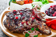 Grilled Ribeye Steak on bone with berry sauce, fresh salad and grilled vegetables on cutting board on wooden background Stock Photos