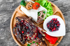 Grilled Ribeye Steak on bone with berry sauce, fresh salad and grilled vegetables on cutting board on wooden background Stock Photo