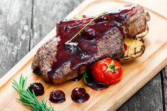 Grilled Ribeye Steak on bone with berry sauce, potatoes, tomatoes and rosemary on cutting board on wooden background Stock Images