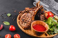 Grilled Ribeye Steak on bone and vegetables with fresh salad and bbq sauce on cutting board over black stone background. Hot Meat royalty free stock image