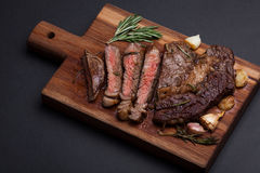 Grilled ribeye steak of marble beef closeup with spices on a wooden Board. Juicy steak medium sliced and ready to eat. With copy space. Top view Royalty Free Stock Photography