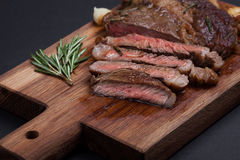 Grilled ribeye steak of marble beef closeup with spices on a wooden Board. Juicy steak medium sliced and ready to eat. With copy space. Top view Stock Photo
