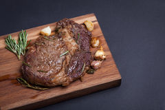 Grilled ribeye steak of marble beef with spices on wooden Board. With copy space royalty free stock photography