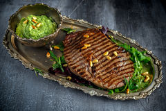 Grilled Ribeye steak served on salad pillow with pesto, pine nuts on a vitage plate Stock Image