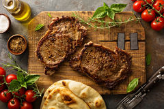 Grilled ribeye steaks on a wooden board Stock Images