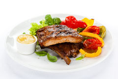 Grilled ribs. Tasty grilled ribs with vegetables royalty free stock photography
