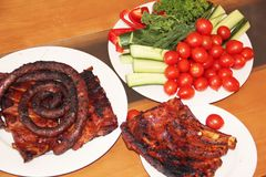 Grilled ribs and sausages with vegetables Stock Image
