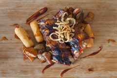 Grilled ribs topped with barbecue sauce and onion rings Royalty Free Stock Photos