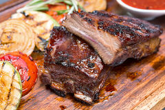 Grilled ribs on a wooden board with vegetables Stock Images