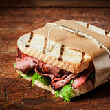 Grilled roast beef sandwich in a takeaway wrapper Stock Images