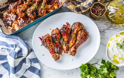 Grilled roasted and barbecue chicken legs on white plate. Grilled roasted and barbecue chicken legs on white plate with herb decoration stock photography