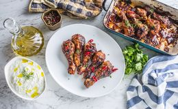 Grilled roasted and barbecue chicken legs on white plate. Grilled roasted and barbecue chicken legs on white plate with herb decoration royalty free stock image