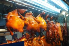 Grilled and roasted chicken is hung in a row. In the glass cabinet for sale stock photography