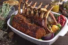 Grilled roasted rack of lamb chops with vegetables, in ceramic baking dish royalty free stock photography