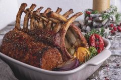 Grilled roasted rack of lamb chops with vegetables in ceramic baking dish. New Year christmas composition,decoration. stock images