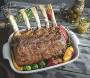 Grilled roasted rack of veal lamb chops with vegetables in ceramic baking dish. royalty free stock photo